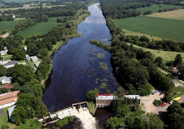 Oil and water flow over Ceresco Dam as oil spill cleanup continues Thursday along the Kalamazoo River. / Andre J. Jackson/Detroit Free Press